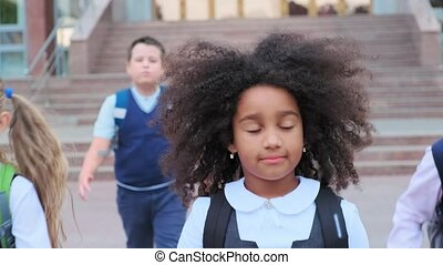 African-American girl with classmates walks in school yard...