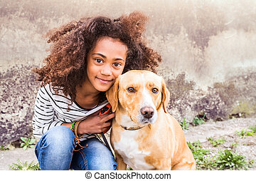 African american girl with her dog against concrete wall. -...