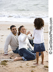 African-American girl with parents on beach