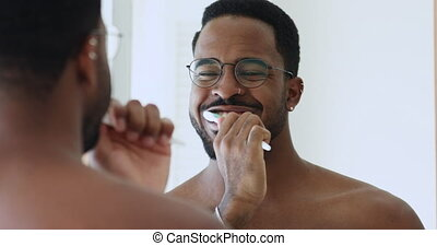African american hipster guy wearing glasses holding toothbrush brushing healthy white teeth with toothpaste looking in bathroom mirror. Morning dental care for caries prevention and gums protection.