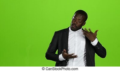 African american guy dances in a business suit, he has funny moves. Green screen. Slow motion