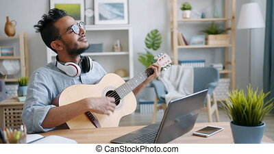 African American guy playing the guitar and using laptop indoors at home