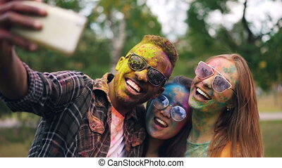 African American guy wearing sunglasses is taking selfie with female friends at Holi color holiday, their faces and hair are dirty with multicolor paint.