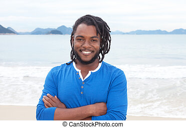 African american guy with dreadlocks and crossed arms at...