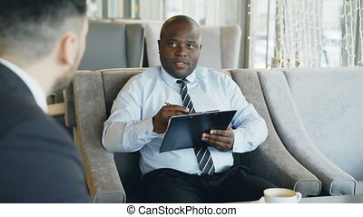African american HR manager having job interview with young man in suit and watching his resume application in modern cafe during coffee break