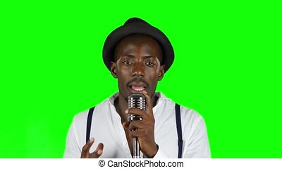 African American in a studio is singing songs into a microphone. Green screen. Close up