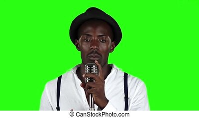 African American in a studio is singing songs into a microphone. Green screen. Slow motion. Close up