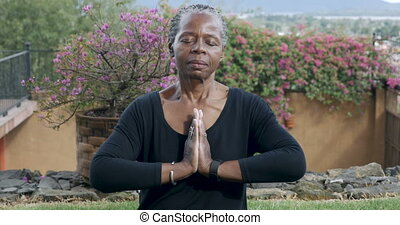 African American in lotus pose finishing with a namaste...