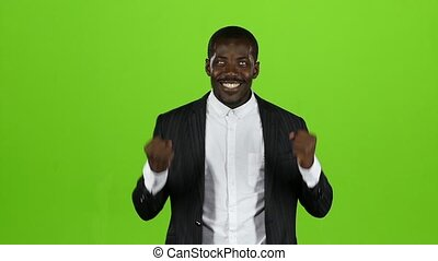 African american in the strict black suit is happy with his victory. Green Screen. Slow motion