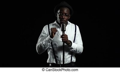 African American is listening to the microphone in the studio. Black background. Slow motion. Close up