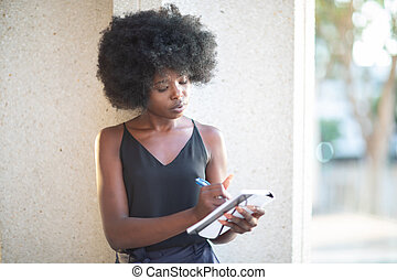 African American lady writing notes leaning on a wall of a concrete building