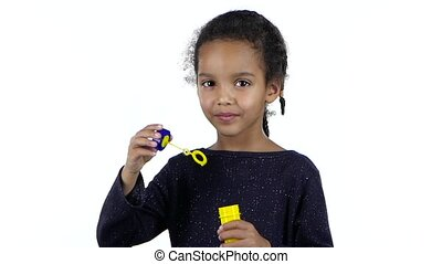 African american little girl's girl lets bubbles. White...