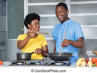 African american love couple cooking at kitchen