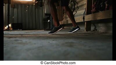 African American male boxer practicing foot movements with ...