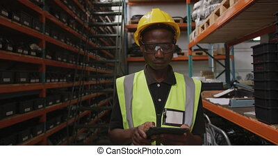 African American male factory worker at a factory wearing a high vis vest using a tablet computer