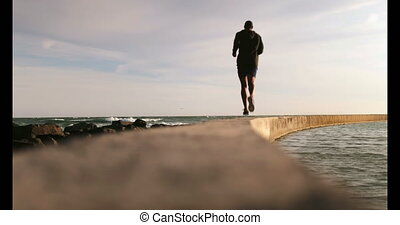 African American male jogger running on the beach 4k