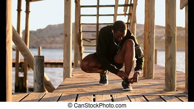 African American male jogger tying shoelace on pier at beach 4k