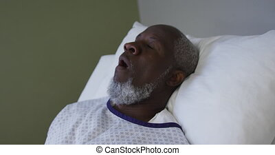African american male patient lying in hospital bed and yawning. medicine, health and healthcare services.