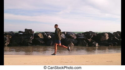 African American male runner jogging on the beach 4k - Side ...