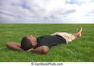 African American Male Student Relaxing in the Grass Outdoors...