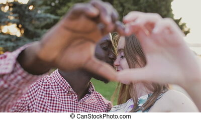 African American man and European girl show heart with hands...
