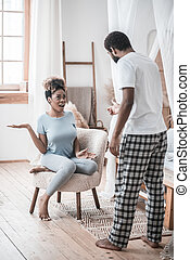 Conflict. African american man standing with his back to camera and sad wife sitting in chair scandalous at home