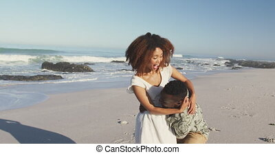 African American man cuddling and holding his wife seaside...