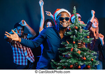 african american man hugging with cristmas tree