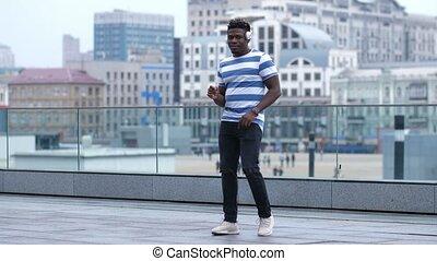 African american man in headphones dancing outdoors - Trendy...