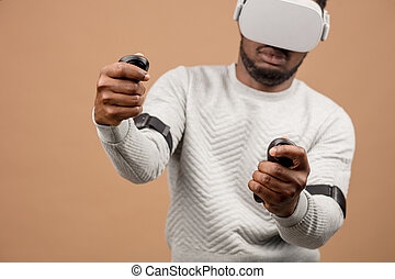 african american man in virtual reality headset playing with joystick while sitting on bean bag chair