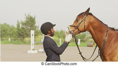 African American man looking at his Dressage horse - Side ...