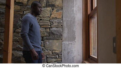 African American man looking through the windows