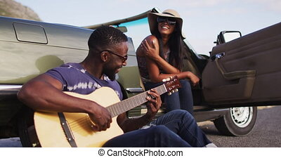 African american man playing guitar for his girlfriend while sitting on the road