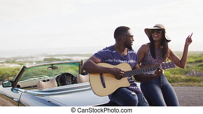 African american man playing guitar for his girlfriend while standing on the road