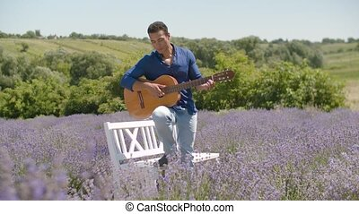 African american man playing guitar in field