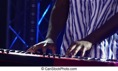 African American man plays piano synthesizer keyboard and sings in dark studio with blue lights. Musician with white ethnic pattern on his face in national striped shirt performs on stage. African folklore. Close up.