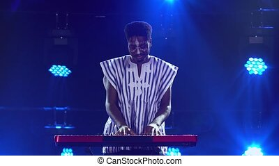 African American man plays piano synthesizer keyboard and sings in dark studio with blue lights. Musician with white ethnic pattern on his face in national striped shirt performs on stage. African folklore.