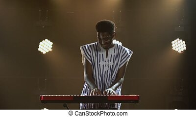 African American man plays piano synthesizer keyboard and sings in dark studio with bright lights. Musician with white ethnic pattern on his face in national striped shirt performs on stage. African folklore.
