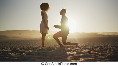 African American man proposing wedding at beach - Front view...