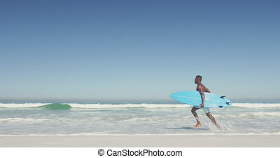 African American man ready to go surf - Side view of an ...