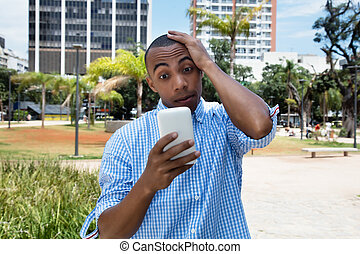 African american man receiving text message with bad news