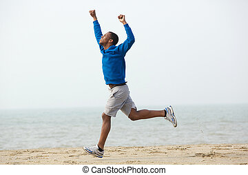 African american man running with hands raised at the beach