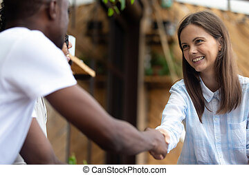 African American man shaking hand of smiling woman close up