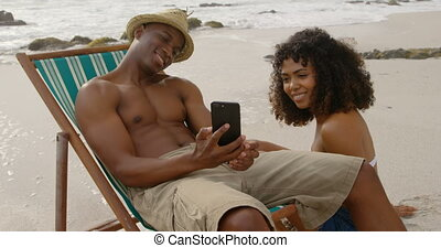 African american man showing photos to woman on mobile phone at beach. They are relaxing together 4k