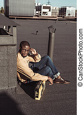 african american man sitting on rooftop with boombox