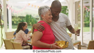 African American man spending time in garden, embracing his mother, with family sitting at a dinner table in the background, in slow motion.