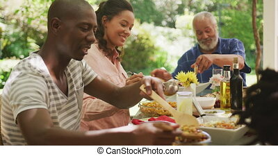 African American man spending time in garden, sitting at a dinner table with his family, putting food on a plate, in slow motion.