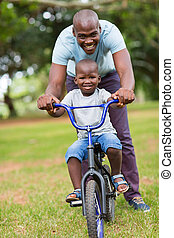 african american man teaching son to ride a bicycle