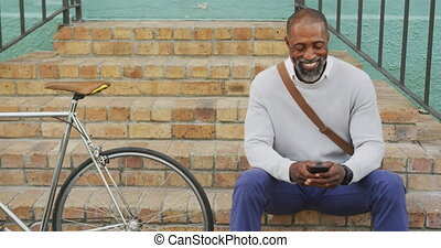 African American man using his phone in the street