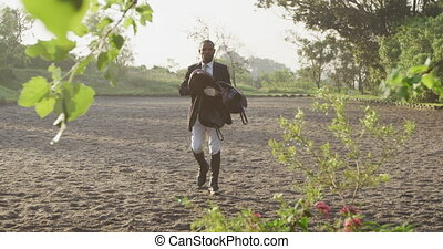 African American man walking with the saddle of Dressage ...